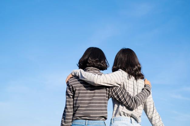 青い空と2人の若い女の子をバックアップします幸せな若い女の子