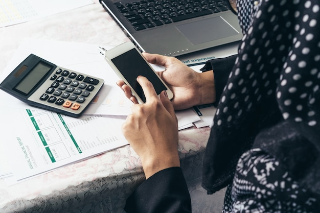 The backside of business muslim woman working  a mobile phone and laptop, calculator,report on .