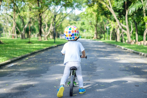 Backside of cute asian 2 years toddler boy child wearing safety helmet learning