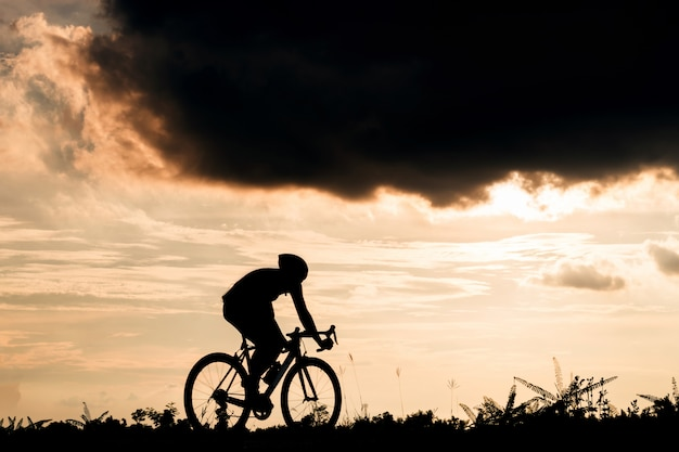 Backside of cyclist ride bicycle at sunset