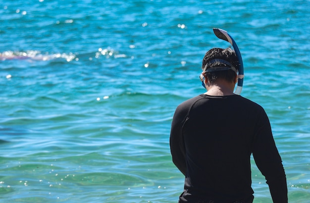 Backside of a man wearing snorkel to diving under sea water.