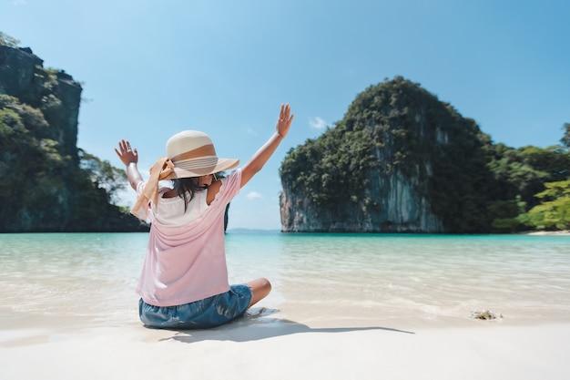 Задняя часть азиатской детской девочки в шляпе, сидящей на пляже.