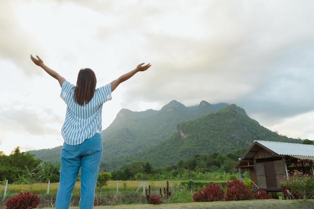 休暇旅行中、女性の裏側は山と空の美しい自然を楽しんでいます。
