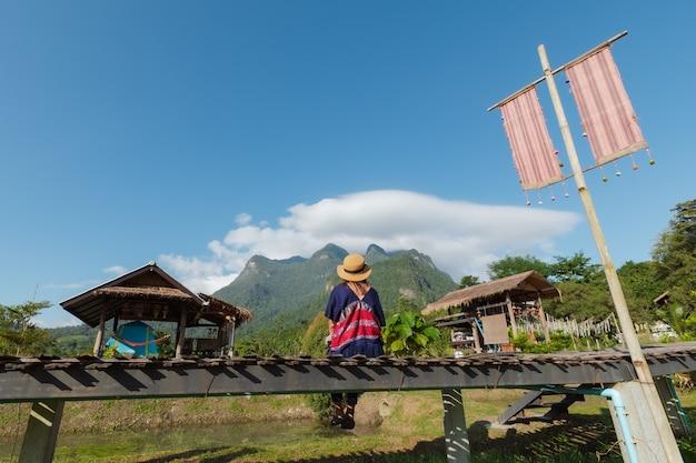 女性の裏側は橋の上に座って、休暇で旅行している間、山と空の美しい自然を楽しんでいます。