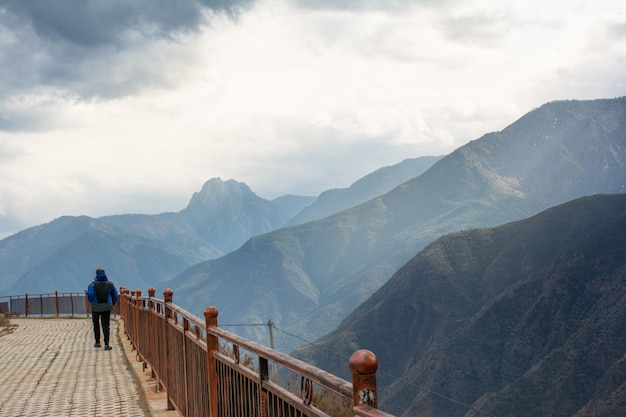Backside of one man walk on bridge by the side of range green high mountain in lijiang, china.