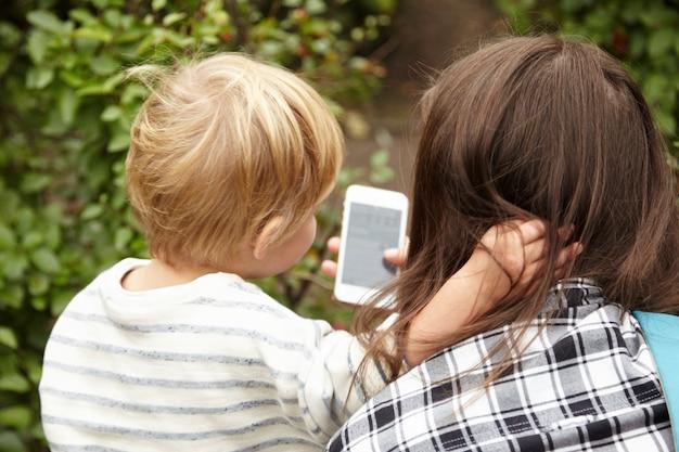 Оборотный портрет матери и сына снаружи. светлые волосы маленького мальчика контрастируют с каштановыми волосами женщины. два человека с интересом смотрят на смартфон, ребенок обнимает женщину вокруг шеи.