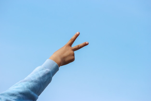 Backside of a victory sign from a young girl hand with blue sky as background.