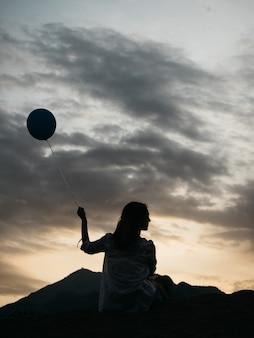 青いヘリウム気球とビーチに座っている若い女性の背面図。