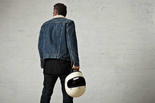 Backside view of young motor biker wears shearling denim jacket and black blank henley shirt, walkinf away and holds vintage beige motorcycle helmet, isolated in center of white brick wall