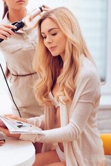 무대 뒤에서. 미용사가 화장실에서 컬링 지팡이로 머리를 컬링하는 동안 잡지를 읽는 아름다운 젊은 여성