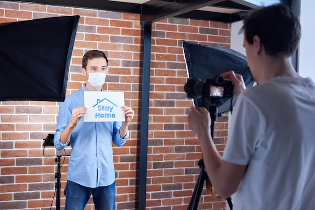 Dietro le quinte dell'uomo caucasico che parla con macchina fotografica nella mascherina medica