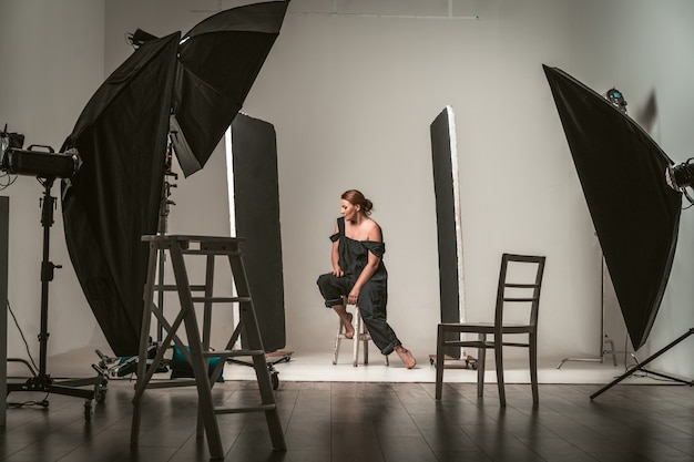 Backstage shooting attractive model in black dress.