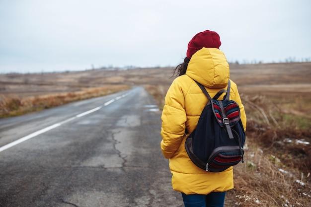 黄色いジャケットと赤い帽子をかぶったバックパックを持った女性観光客の後ろ姿が道を歩きます。