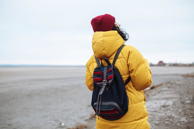 広大な空の冬の谷の低地の間で脇道を歩いているバックパックを持つ若い女性観光客の背景。黄色のジャケットと赤い帽子をかぶった女性旅行者。ヒッチハイク、旅行のコンセプト。