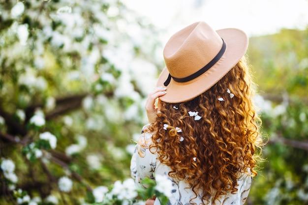 春の公園で咲く花の木の近くに立っているベージュの帽子と白いドレスを着て巻き毛に花を持つ若い女性の背景。