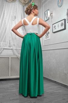 Обратный взгляд девушка позирует в белом и зеленом вечернем платье.