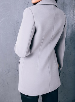 Вид сзади женщины в сером пиджаке с кошельком