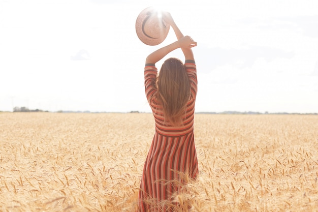 Backview of slender well shaped woman holding her arms up, having straw hat in one hand, standing in front of sun with pleasure in middle of wheat field, enjoying summer holidays at rural area.