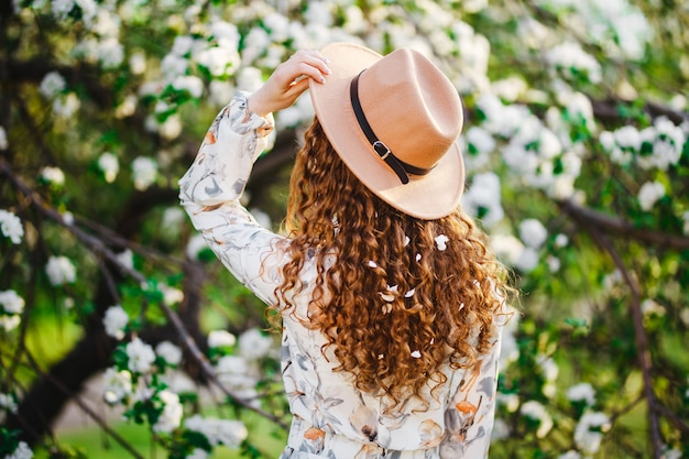 Backview of a young woman with blossom in her curly hair wearing beige hat and white dress standing near the blooming flowering tree at the spring park.