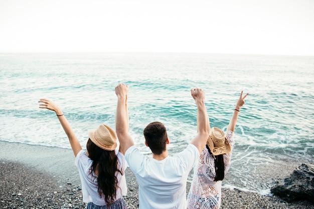 Backview друзей на пляже, поднимающих оружие