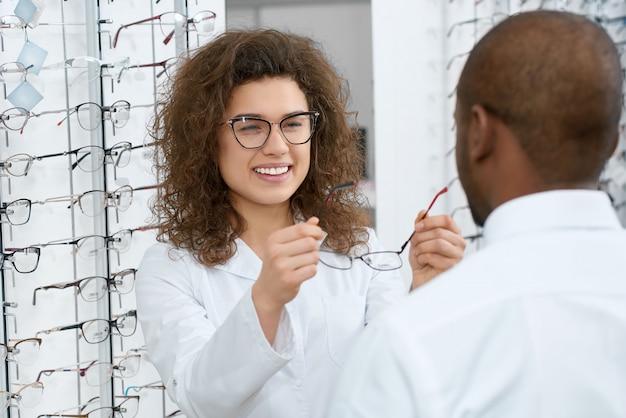 Backview человека примеряет очки в оптическом магазине.