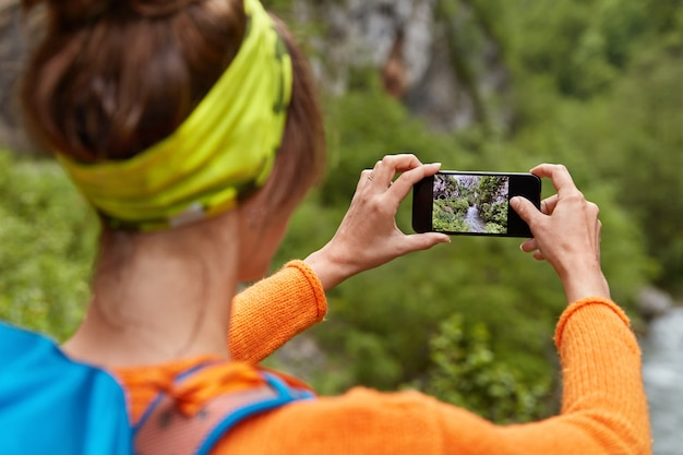 Backwards shot of woman tourist makes photo of river in ravine on smartphone device for posting in social networks
