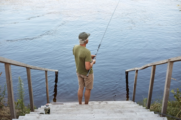 Backwards view of man catching fish while posing on wooden stairs leading to lake, male wearing casual attire, enjoying beautiful nature and fishing.