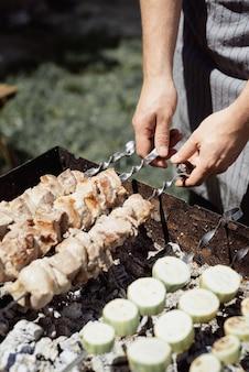 뒤뜰 바베큐. 금속 꼬치에 케밥과 야채를 굽고 손 망.