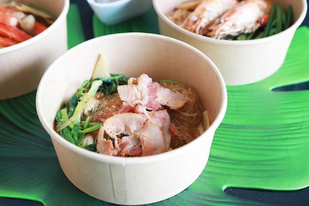 Стеклянная запеченная с беконом лапша и овощи в бумажной миске, любимое блюдо азиатской кухни.