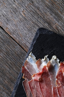 Bacon on black stone plate, top view