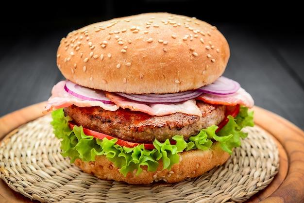 ビーフカツレツ、ベーコンハンバーガー、新鮮な野菜、木製の背景に