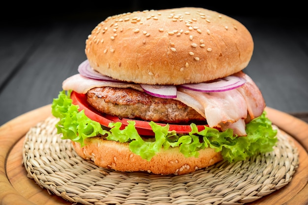 Bacon burger with beef cutlet, with fresh vegetables, on wooden background