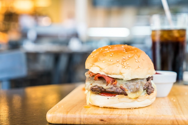Bacon cheese burger with beef on wood board in restaurant