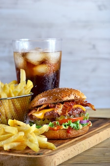 Bacon and cheese burger with french fries and a glass of cola