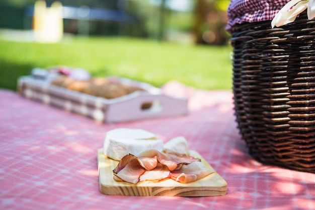 Bacon and cheese on chopping board over the cloth in the picnic