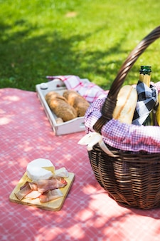 Bacon and cheese on chopping board over the cloth with picnic basket
