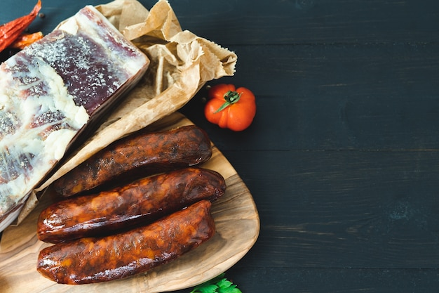 Bacon and cured sausages on a dark background. copy space.