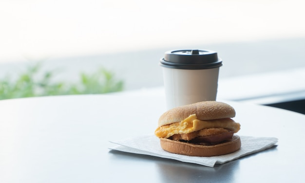 Bacon and omelette hamburger on the paper with white paper coffee mug on the table in fast food restaurant