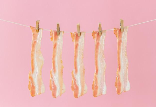 ピンクの背景にベーコン。フードスタイル。ミニマリズム。アート。
