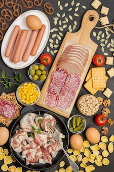 Bacon in pan, salami ham on cutting board, sausages in white plate, vegetables, cookies. ingredients for english breakfast
