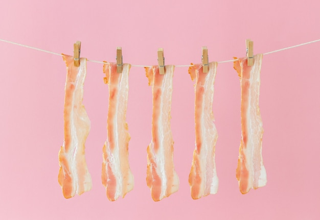 Bacon on a pink background. food style. minimalism. art.