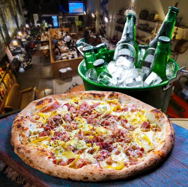 Bacon pizza, beer in an ice bucket at the pizzeria