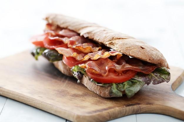 木製のまな板にベーコンサンドイッチ