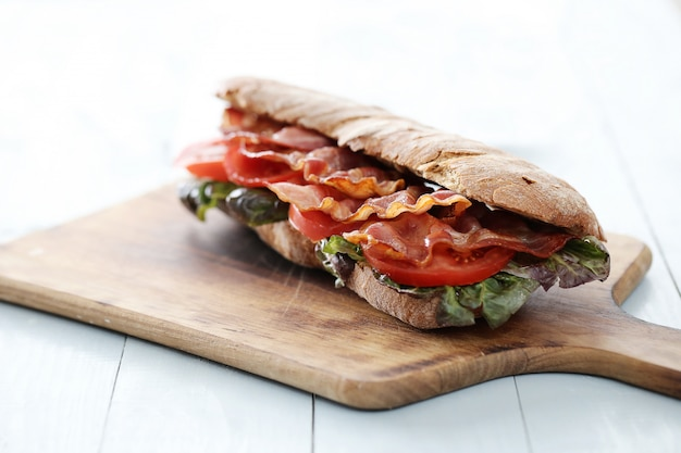 Bacon sandwich on wooden cutting board