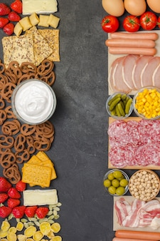 Bacon, sausages, cheese, vegetables, cookies, cereal yogurt: ingredients for continental breakfast.
