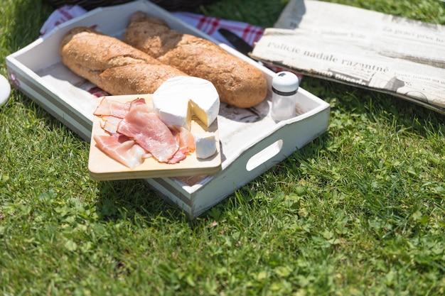 Бэкон с сыром и хлебом на зеленой траве