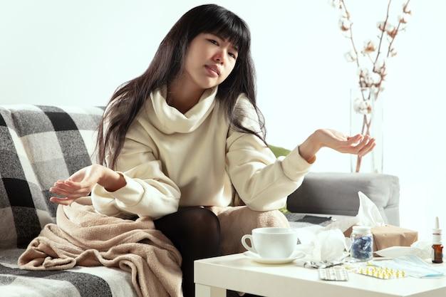 格子縞に包まれた細菌の若い女性は、くしゃみや咳をして病気に見えます