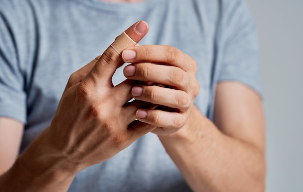 Bactericidal plaster on the finger of a man in a t-shirt on a gray space