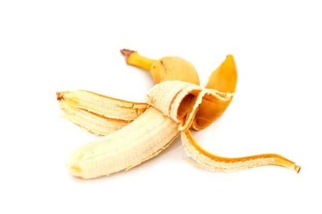 나쁜 바나나 흰색 배경에 고립입니다. 껍질을 벗긴 오래된 바나나. 열대 노란색 과일. 선택적 초점입니다. 적절한 영양의 개념입니다. 비문 또는 로고를 위한 장소