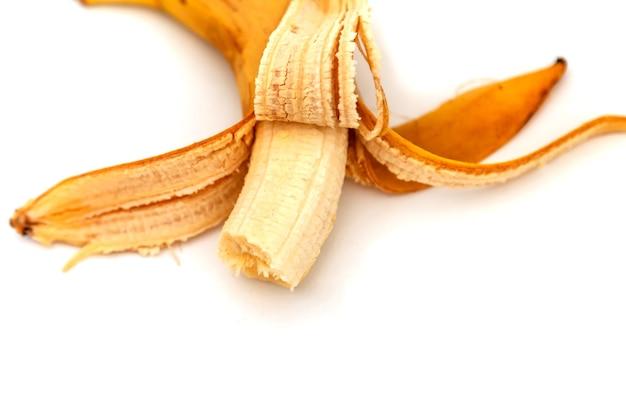 나쁜 물린 바나나 흰색 배경에 고립입니다. 껍질을 벗긴 오래된 바나나. 열대 노란색 과일. 선택적 초점입니다. 적절한 영양의 개념입니다. 비문 또는 로고를 위한 장소